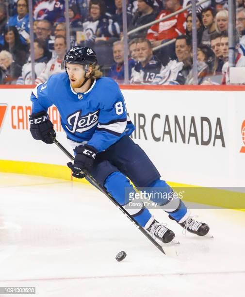 Kyle Connor of the Winnipeg Jets plays the puck around the boards during first period action against the Detroit Red Wings at the Bell MTS Place on...