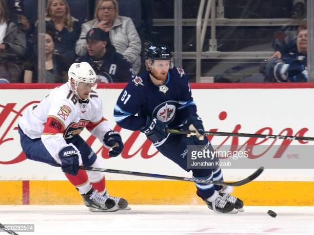 Kyle Connor of the Winnipeg Jets plays the puck away from Aleksander Barkov of the Florida Panthers during first period action at the Bell MTS Place...