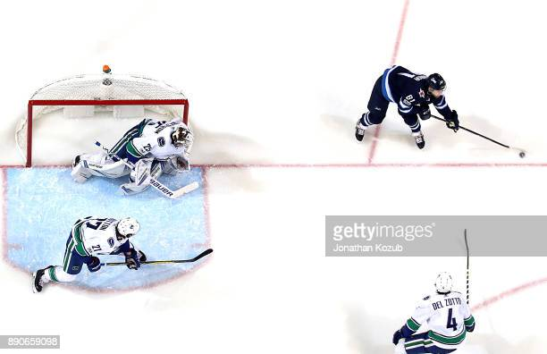 Kyle Connor of the Winnipeg Jets plays the puck to the side of the net as Ben Hutton goaltender Jacob Markstrom and Michael Del Zotto of the...
