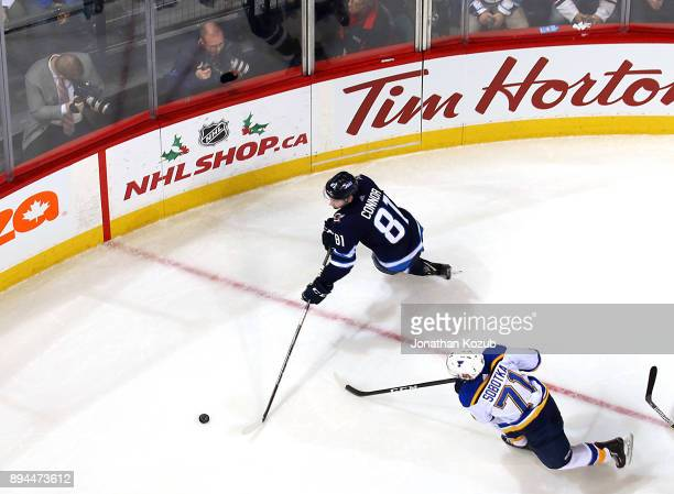 Kyle Connor of the Winnipeg Jets plays the puck up the ice as Vladimir Sobotka of the St Louis Blues gives chase during second period action at the...