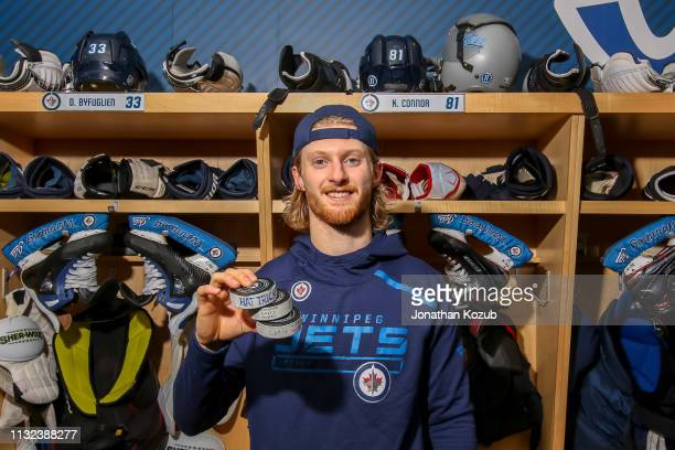 Kyle Connor of the Winnipeg Jets poses with his game pucks after scoring his first career NHL hat trick against the Nashville Predators in a 50...