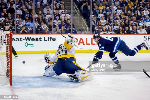 Kyle Connor of the Winnipeg Jets shovels the puck past the outstretched glove on goaltender Pekka Rinne of the Nashville Predators for a second...
