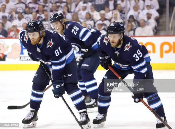 Kyle Connor Patrik Laine and Toby Enstrom of the Winnipeg Jets get set during a second period faceoff against the Nashville Predators in Game Four of...
