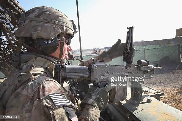 Kyle Cooper with the US Army's 4th squadron 2d Cavalry Regiment loads his machinegun before heading out on patrol on February 28 2014 near Kandahar...