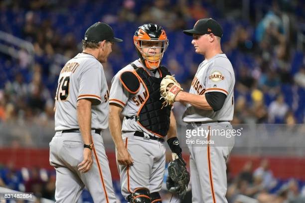 Kyle Crick of the San Francisco Giants talks with Pitching Coach Dave Righetti and Catcher Nick Hundley during the seventh inning against the Miami...
