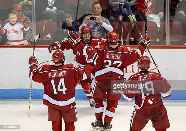 Kyle Criscuolo of the Harvard Crimson celebrates his overtime winning goal against the Boston University Terriers with his teammates Alexander...