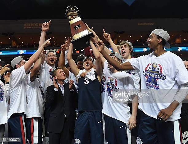 Kyle Dranginis of the Gonzaga Bulldogs holds up the trophy as he celebrates with teammates and head coach Mark Few after they defeated the Saint...