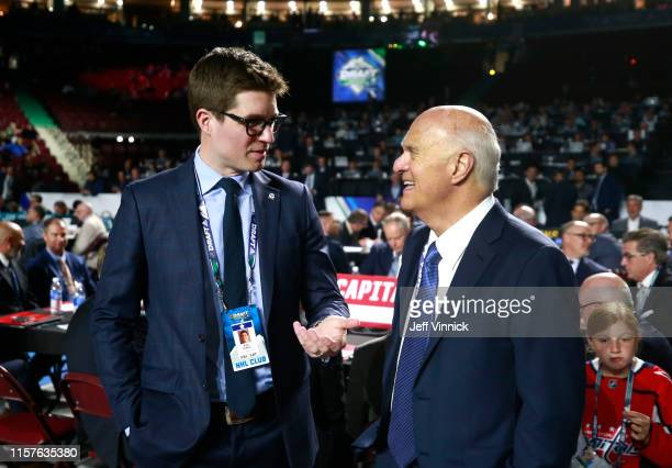 Kyle Dubas of the Toronto Maple Leafs and general manager Lou Lamoriello of the New York Islanders talk on the draft floor during Rounds 2-7 of the...