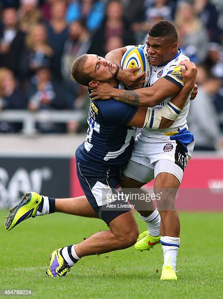 Kyle Eastmond of Bath Rugby is tackled by Mark Jennings of Sale Sharks during the Aviva Premiership match between Sale Sharks and Bath at AJ Bell...