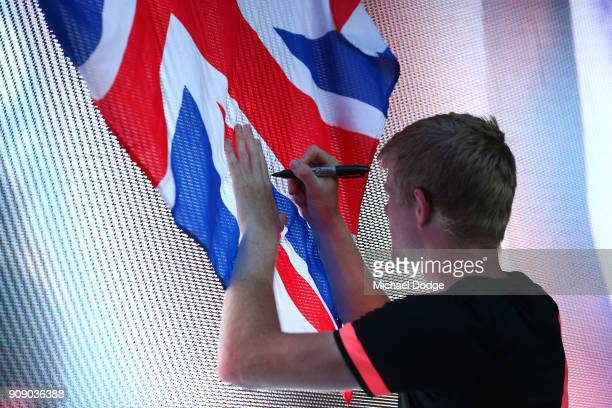 Kyle Edmund of Great Britain signs autographs for fans after winning his quarterfinal match against Grigor Dimitrov of Bulgaria on day nine of the...