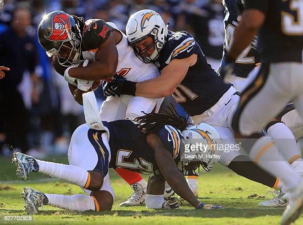 Kyle Emanuel and Jahleel Addae of the San Diego Chargers bring down Jacquizz Rodgers of the Tampa Bay Buccaneers during the first half of a game at...
