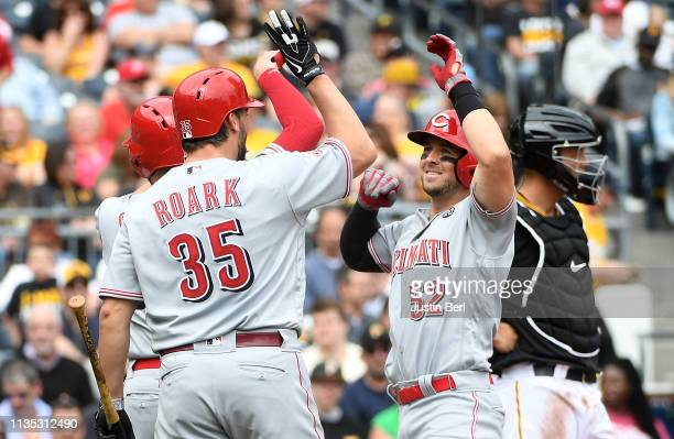 Kyle Farmer of the Cincinnati Reds high fives with Tanner Roark after hitting a two run home run in the third inning during the game against the...