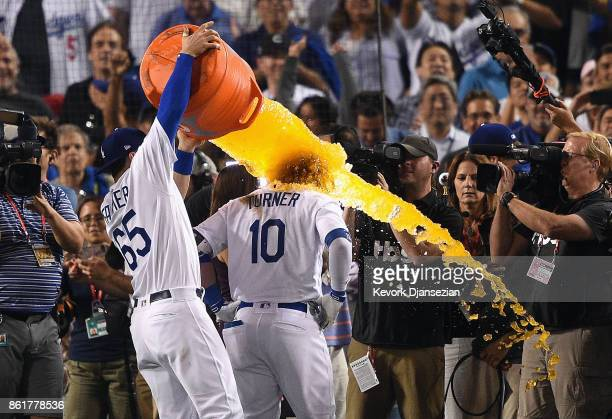 Kyle Farmer of the Los Angeles Dodgers dunks Justin Turner with Gatorade after Turner hit a threerun walkoff home run in the ninth inning to defeat...