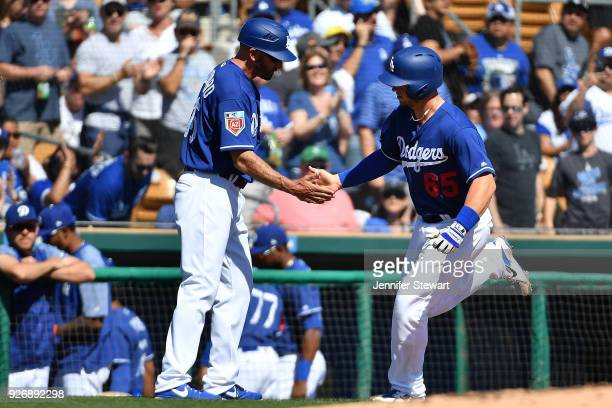 Kyle Farmer of the Los Angeles Dodgers is congratulated by third base coach Chris Woodward after hitting a solo home run in the first inning of the...