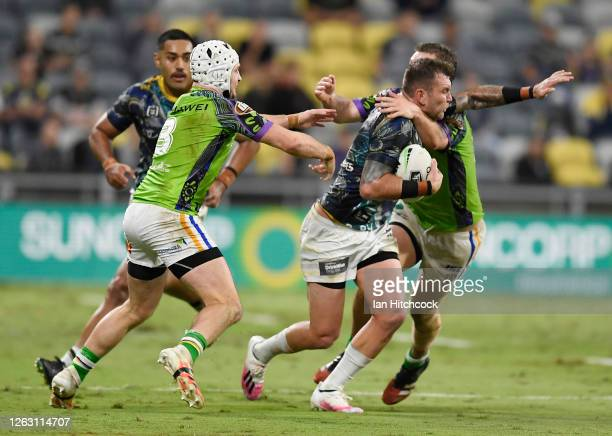 Kyle Feldt of the Cowboys is wrapped up by the Raiders defence during the round 12 NRL match between the North Queensland Cowboys and the Canberra...
