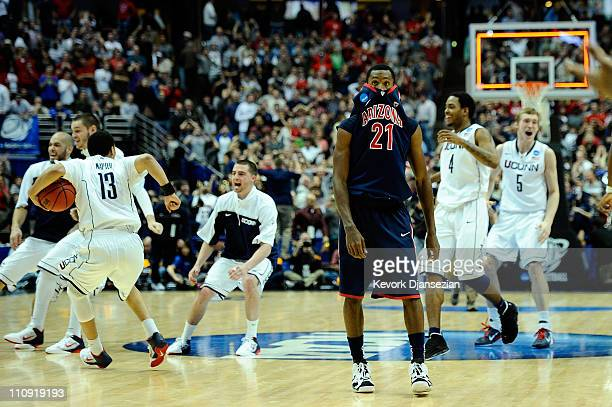 Kyle Fogg of the Arizona Wildcats reacts after losing to the Connecticut Huskies as they celebrate behind him during the west regional final of the...