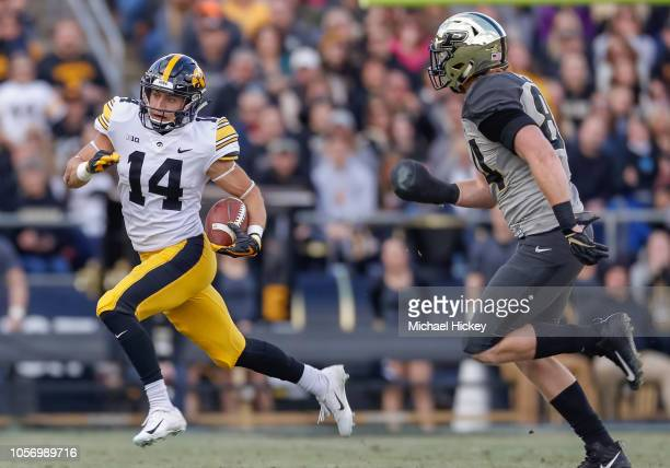 Kyle Groeneweg of the Iowa Hawkeyes runs the ball as Jess Trussell of the Purdue Boilermakers pursues at Ross-Ade Stadium on November 3, 2018 in West...
