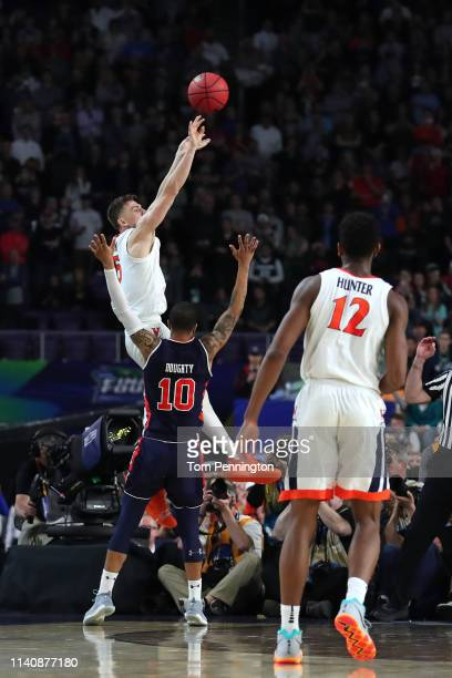 Kyle Guy of the Virginia Cavaliers attempts a three point basket as he is defended by Samir Doughty of the Auburn Tigers in the second half during...