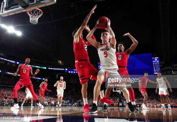 Kyle Guy of the Virginia Cavaliers is defended by Davide Moretti and Kyler Edwards of the Texas Tech Red Raiders in the first half during the 2019...