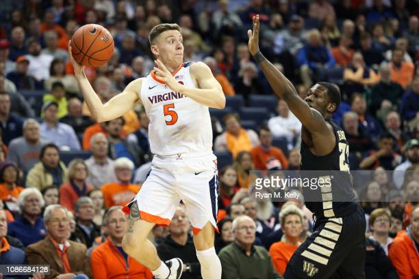 Kyle Guy of the Virginia Cavaliers passes around Chaundee Brown of the Wake Forest Demon Deacons in the second half during a game at John Paul Jones...