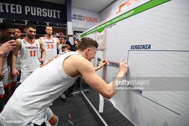 Kyle Guy of the Virginia Cavaliers places his team's name in the bracket in the Virginia locker room after winning the semifinal game in the NCAA...