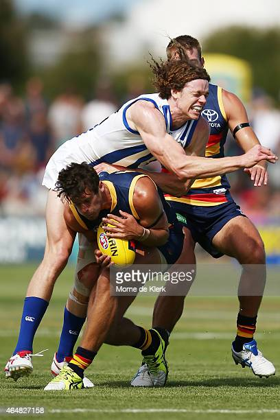 Kyle Hartigan of the Crows is tackled by Ben Brown of North Melbourne during the NAB Challenge AFL match between the Adelaide Crows and the North...