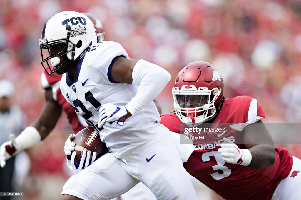 Kyle Hicks #21 of the TCU Horned Frogs runs the ball and is chased by McTelvin Agim #3 of the Arkansas Razorbacks at Donald W. Reynolds Razorback Stadium on September 9, 2017 in Fayetteville, Arkansas. The Horn Frogs defeated the Razorbacks 28-7.