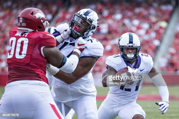 Kyle Hicks runs the ball behind the blocking of Lucas Niang of the TCU Horned Frogs during a game against the Arkansas Razorbacks at Donald W...