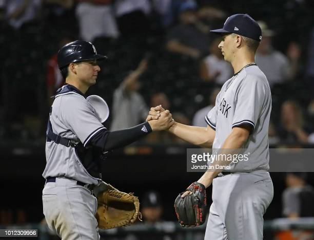 Kyle Higashioka and AJ Cole of the New York Yankees shake hands after a win over the Chicago White Sox at Guaranteed Rate Field on August 6 2018 in...