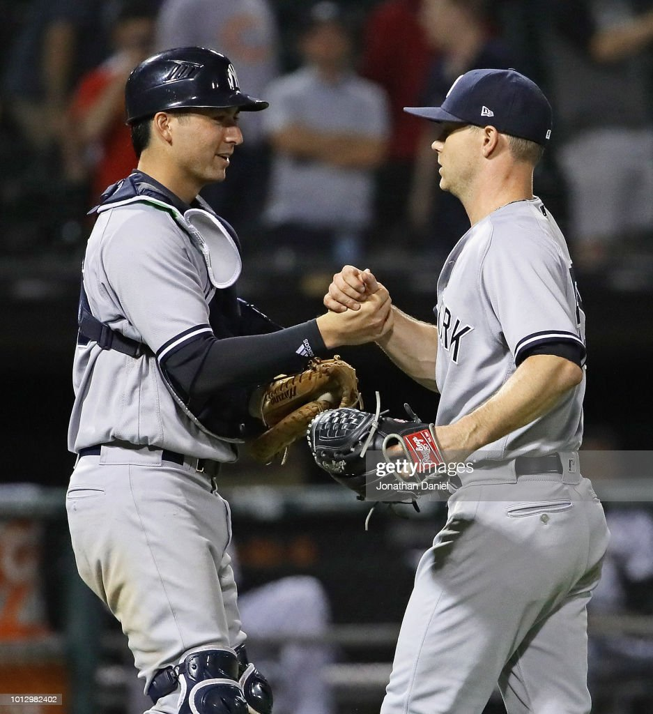 Kyle Higashioka #66 (L) and Sonny Gray #55 of the New York Yankees shake hands after win against the Chicago White Sox at Guaranteed Rate Field on August 7, 2018 in Chicago, Illinois. The Yankees defeated the White Sox 4-3 in 13 innings.