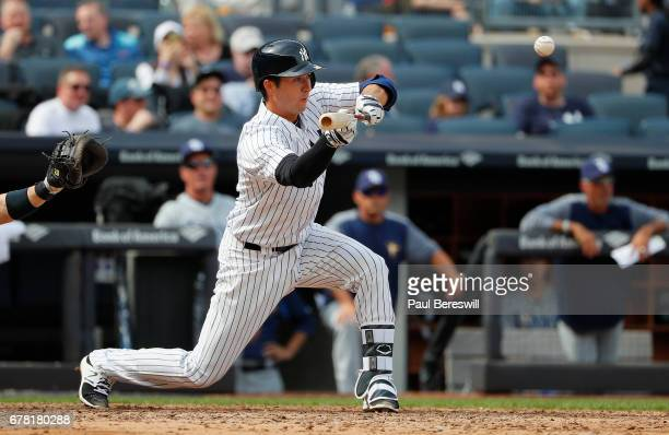 Kyle Higashioka of the New York Yankees bunts in an MLB baseball game against the Tampa Bay Rays on April 12 2017 at Yankee Stadium in the Bronx...