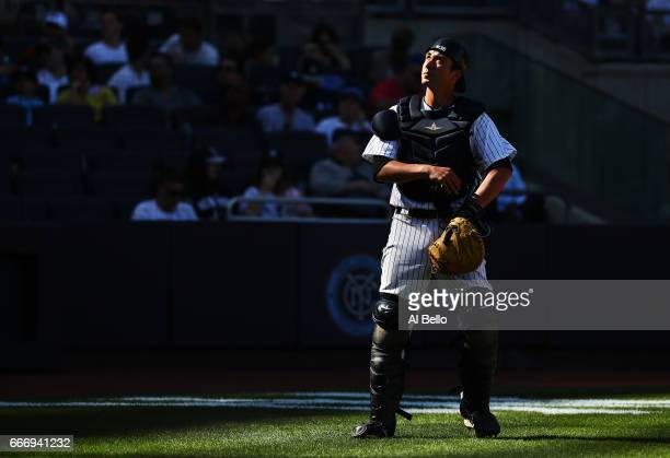 Kyle Higashioka of the New York Yankees looks off a fould ball against the Tampa Bay Rays during the New York Yankees home Opening game at Yankee...