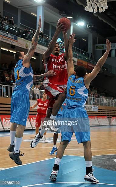 Kyle Hines of Brose is challenged by Joseph Buck and Dorian McDaniel of Duesseldorf during the Beko Basketball Bundesliga match between Gloria Giants...