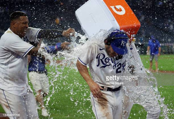 Kyle Isbel of the Kansas City Royals is doused with water by Salvador Perez and Whit Merrifield after the Royals defeated the Oakland Athletics 10-7...