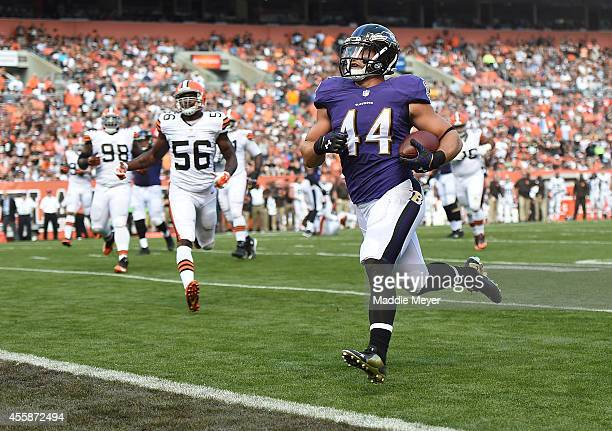 Kyle Juszczyk of the Baltimore Ravens carries the ball for a touchdown in front of Karlos Dansby of the Cleveland Browns during the second quarter at...