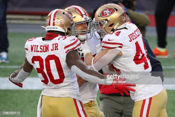 Kyle Juszczyk of the San Francisco 49ers celebrates his touchdown against the New England Patriots with Jeff Wilson Jr. #30 and George Kittle during...
