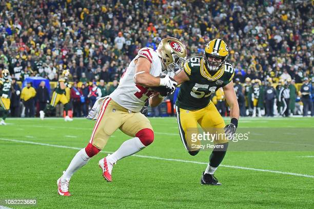 Kyle Juszczyk of the San Francisco 49ers is brought down by Kyler Fackrell of the Green Bay Packers during the second half at Lambeau Field on...