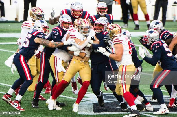 Kyle Juszczyk of the San Francisco 49ers is tackled by members of the New England Patriots in the first half at Gillette Stadium on October 25, 2020...