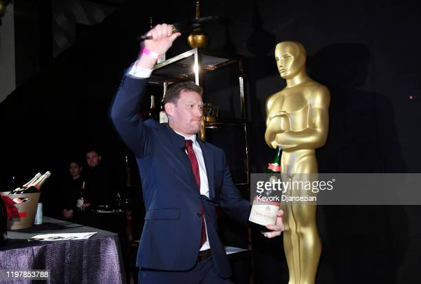 Kyle Kaplan opens a Piper-Heidsieck champagne with his sword during the Governors Ball press preview for the 92nd Annual Academy Awards on January...