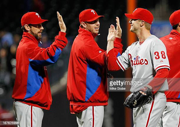 Kyle Kendrick of the Philadelphia Phillies celebrates with teammate Roy Halladay and Cliff Lee after pitching a complete game shutout against the New...