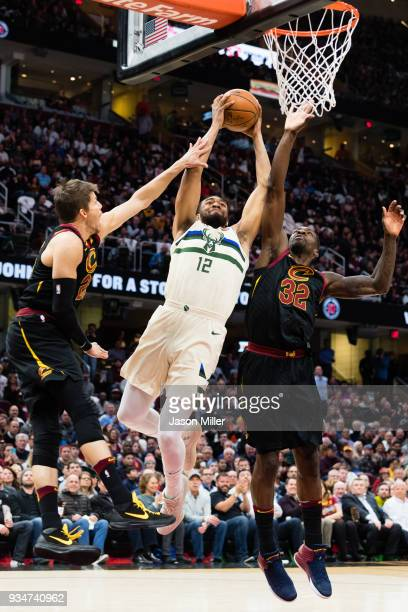 Kyle Korver and Jeff Green of the Cleveland Cavaliers try to block Jabari Parker of the Milwaukee Bucks during the first half at Quicken Loans Arena...