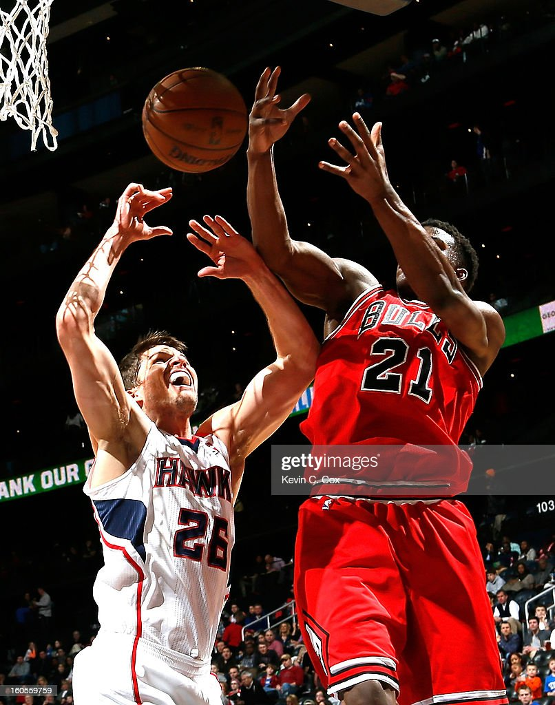 Kyle Korver #26 of the Atlanta Hawks battles for a rebound against Jimmy Butler #21 of the Chicago Bulls at Philips Arena on February 2, 2013 in Atlanta, Georgia.