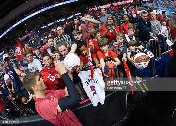 Kyle Korver of the Atlanta Hawks signs autographs for some fans before the game against the Brooklyn Nets in Game One of the Eastern Conference...