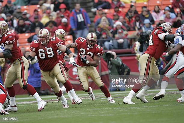 Kyle Kosier of the San Francisco 49ers blocks as Kevan Barlow runs with the ball against the Buffalo Bills at Monster Park on December 26 2004 in San...