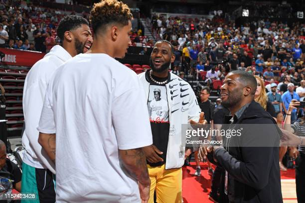 Kyle Kumza Anthony Davis and Lebron James of the Los Angeles talks with Brandon Weems before the game between the Los Angeles Lakers and the LA...