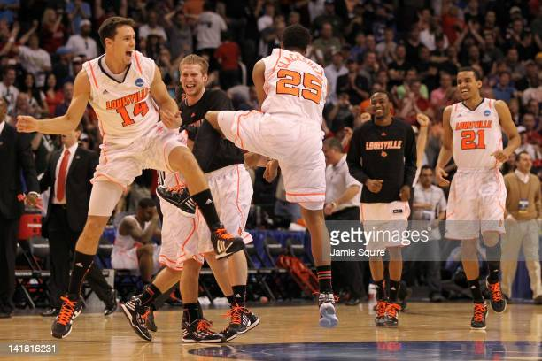 Kyle Kuric and Wayne Blackshear of the Louisville Cardinals celebrate with teammates after defeating the Florida Gators 7268 during the 2012 NCAA...