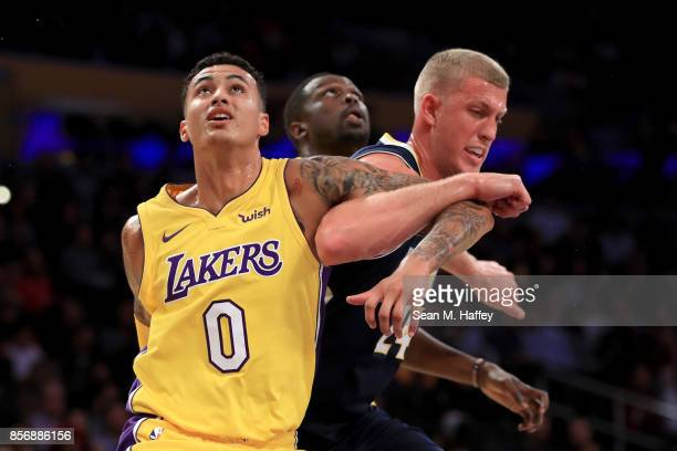 Kyle Kuzma and Luol Deng of the Los Angeles Lakers defend against Mason Plumlee of the Denver Nuggets during the second half of a preseason game at...