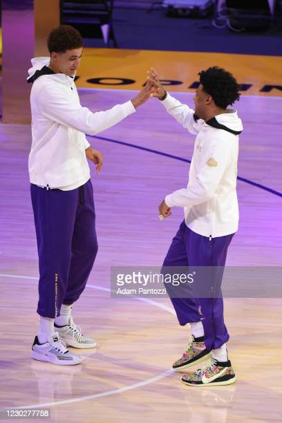 Kyle Kuzma and Quinn Cook of the Los Angeles Lakers react as they get their 2019-20 NBA Championship rings during the ring ceremony before the game...