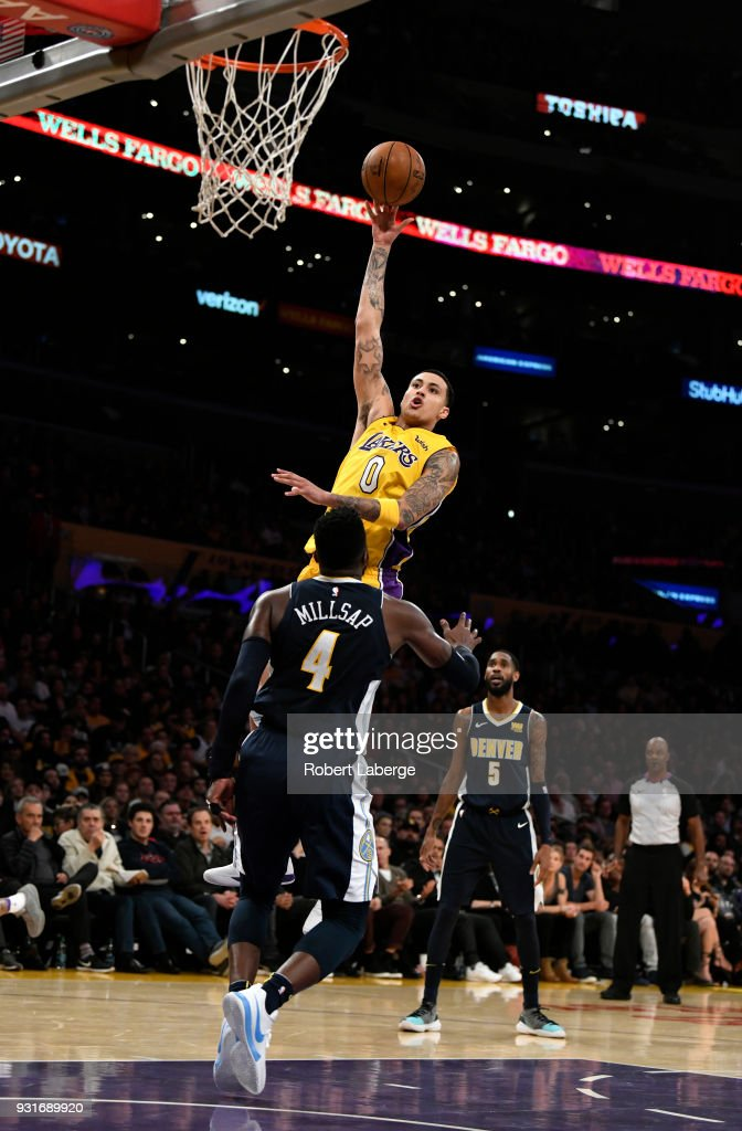 Kyle Kuzma #0 of the Los Angeles Lakers attempts a shot against Paul Millsap #4 of the Denver Nuggets on March 13, 2018 at STAPLES Center in Los Angeles, California.