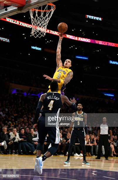 Kyle Kuzma of the Los Angeles Lakers attempts a shot against Paul Millsap of the Denver Nuggets on March 13 2018 at STAPLES Center in Los Angeles...